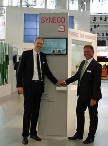 (Von links) Marcus Wittmann, Leiter Fenster und Fassade, und Jürgen Hoffmann, Leiter Marketing und Sales Zentraleuropa, beim Start des SYNEGO Countdowns auf der fensterbau frontale 2014