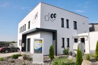 Frontansicht des Gebäudes mit dem Haupteingang sowie eines Outdoordisplays der Eigenmarke Promoscreen