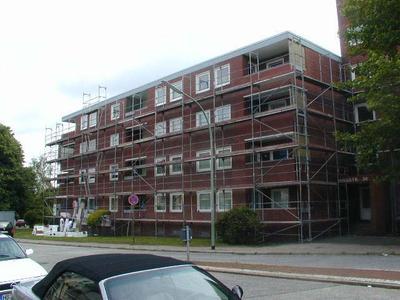 (Alte Fassade) Das Gebäude während der Sanierung: Die Klinkerverblendungen wurden in Teilen durch ein Wärmedämm-Verbundsystem ersetzt und anschließend verputzt.