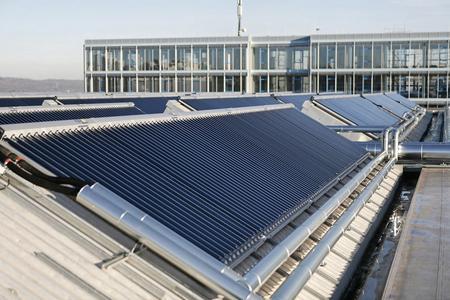 """""""Teil des Kollektorfeldes und des Nachbargebäudes, das mit Solarwärme und -kälte versorgt wird"""" (Quelle: Festo)"""