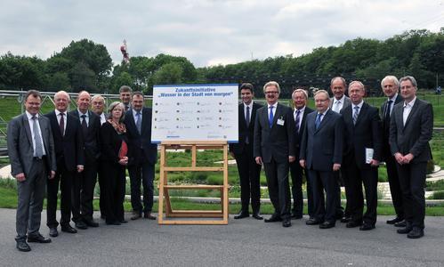 Gruppenfoto, auf dem die Vertreter der Städte gemeinsam mit Dr. Jochen Stemplewski, dem Vorstandsvorsitzenden der Emschergenossenschaft, im Bottroper BernePark die symbolische Unterschriftensammlung präsentieren (Foto: TIM FOLTIN/Emschergenossenschaft)