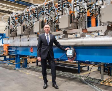 Gerold Keune im Hertwich-Werk vor einer der leistungsfähigsten Ultraschallprüfanlagen mit bis zu AA-Prüfqualität und intuitiven Bedienfunktionen