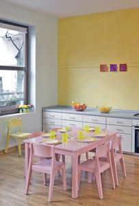 Montessori-Kinderzentrum in Frankfurt/Sachsenhausen: Auch im gelben Gruppenraum kommen die vorhandenen rosa Möbel mit hellblauen Wänden und gelb lasierter Wand (ArteLasur) gut zur Geltung. Durch die Farbverzahnungen wie gelbe Wand – gelbes Geschirr, rosa Möbel – rosa/violette Bilder wird ein stimmiges Erscheinungsbild geprägt. Es entsteht ein zarte