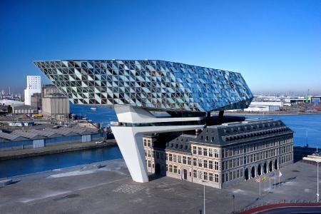 Ein Leuchtturm für die Welt: Das neue Headquarter der Hafenbehörde von Antwerpen ist aus dem Zusammenspiel dreier räumlicher Elemente entstanden: dem denkmalgeschützten Bestandsgebäude, einer Betonbrücke und dem vertikalen Erweiterungsneubau mit Schüco Systemtechnik aus Aluminium / Bildnachweis Schüco International KG
