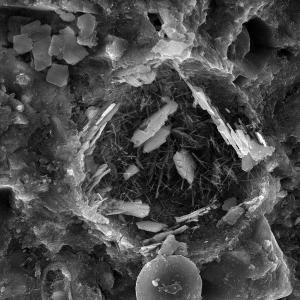 Die neue Betonzusatzmittellinie Centrament Proof C der MC-Bauchemie wird zur kristallinen Abdichtung von Beton eingesetzt. Centrament Proof CL 1 und Centrament Proof CP 10 nutzen die Kristallisation, reduzieren damit die Porosi-tät des Betons und sorgen so für eine dauerhafte Abdichtung des Betons sowie eine Erhöhung der Lebensdauer des Bauwerks.  Die Aufnahme mit dem Rasterelektronenmikroskop zeigt die Kristallbildung im Zementstein-Mikrogefüge bei einer Vergrößerung von 2.000.