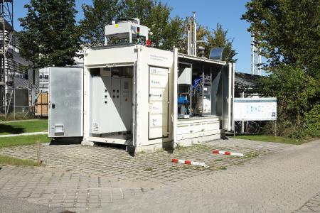 Der Container umfasst zwei getrennte Abteile, eines für die effiziente Anbindung ans elektrische Netz und die Steuerungstechnik (vorne), das andere für den verfahrenstechnischen Aufbau.