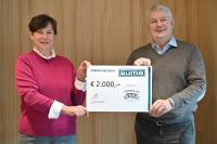 Simone Burk-Seitz (1. Vorsitzende des Kinderbrücke Allgäu e.V.) nimmt dankend den Spendenscheck von SUMA-Geschäftsführer Paul Thürwächter entgegen