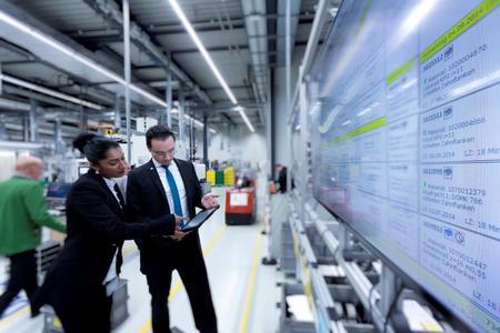 Optimierte Prozesse und Abläufe durch Digitalisierung: WITTENSTEN-Mitarbeiter in der Fellbacher Produktion in Abstimmung an der elektronischen Plantafel