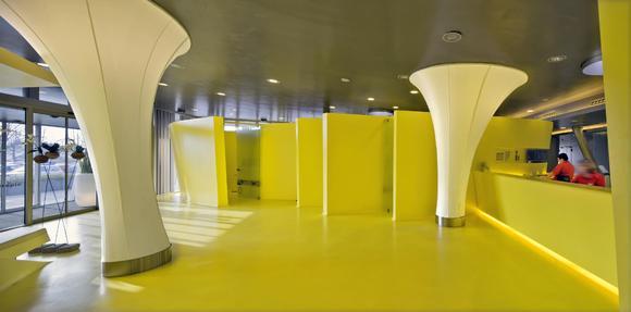 Wie aus einem Guss: Boden und Wand sind mit Caparol Disbon 447 in Gelb beschichtet. Im Empfangsbereich wachsen mit weißem Textil bespannte Leuchten wie Blütenkelche aus dem Boden. Foto: Caparol Farben Lacke Bautenschutz/Martin Duckek