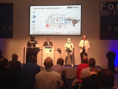 Thomas Wienecke (2. v. l.) und Julian Fay (1. v. r.), beide Senior Presales Consultant bei noris network, während ihres it-sa-Vortrags 2014. Kollegen in Star-Wars-Kostümen stehen symbolisch für Schutz gegen IT-Angriffe