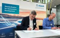 M. Dupuis (VIRES) and Dr. Klaus Estenfeld (ASAM) signing the contract to transfer OpenSCENARIO to ASAM