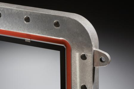 Einbaufertige Sicht- und Schutzscheibe. Die transparente und beschichtete Glaskeramik ist in einen Rahmen aus Aluminium-Druckguss eingeklebt. Die Glaskante ist umlaufend facettiert und ohne scharfe Kanten, um in der Einbausituation Platz für die Dichtung (rot) zu schaffen. Die elektrisch leitende Beschichtung ist mittels Kontaktfedern angebunden (im Bild oben links).  © Irlbacher