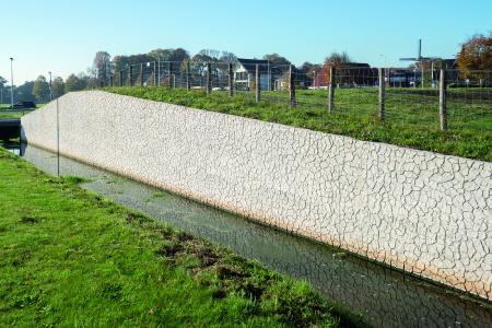 An einen Schnitt durch einen Erdhügel, dessen Ober-fläche getrocknet und gerissen ist, erinnert diese Stützmauer im niederländischen Velsen. Realisiert mit der NOEplast Struktur Santpoort (Foto: NOE-Schaltechnik, Süssen)