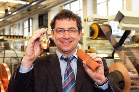 Joachim-Franz Schmidt, Fertigungsleiter Walzwerk bei Heraeus in Hanau, mit dem Bauteil eines walzplattierten Bandes von Heraeus (rechts) und dem Beschleunigungsrohr für den Large Hadron Collider. Der speziell hergestellte Sonderstahl für die Bänder wurde von Heraeus mit einer hauchdünnen Kupferschicht von nur wenigen Mikrometern Dicke plattiert und gleichzeitig mit einem Sägezahn-Spezialprofil versehen. Die Sägezähne dienen der Reflexion der bei den späteren Experimenten aus der Teilchenkollision freigesetzten Strahlung (Foto: Heraeus)