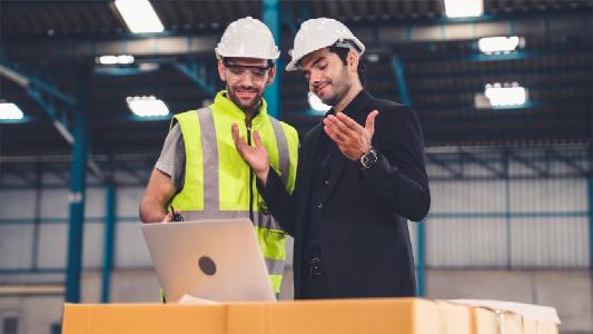 Zwei Arbeiter in einer Produktion diskutieren und arbeiten in einer Halle