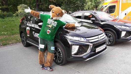 Das Maskottchen der Füchse Berlin Fuchsi posiert vor einem Fahrzeug aus der Flotte von CSB Schimmel Automobile für die Füchse Berlin