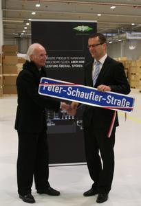 Der Oberbürgermeister der Stadt Rottenburg am Neckar, Stephan Neher, übergibt das Straßenschild an Peter Schaufler (links)