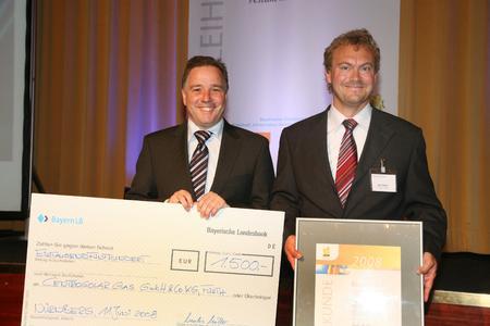 Ralf Ballasch, Geschäftsführer der CENTROSOLAR GLAS GmbH (rechts), nimmt den Preis von Staatssekretär Sackmann entgegen