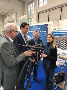 Staatssekretär Eisenreich (2. v. li) ist begeistert von der Leichtigkeit des Carbon Fahrrades am Bildungsstand des Projektes MAI Job und lässt sich von Katharina Lechler (re) Details erklären
