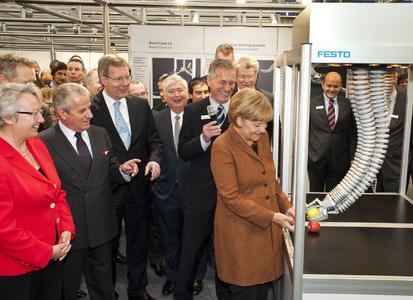 Bundeskanzlerin Dr. Angela Merkel überreicht im Beisein des italienischen Wirtschaftsministers Claudio Scajola und Dr. Eberhard Veit, Vorstandsvorsitzender der Festo AG, dem Bionischen Handling-Assistenten von Festo einen Apfel