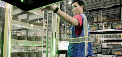 Die Grenzebach Ware-zur-Person Lösung unterstützt GEODIS Mitarbeiter in der Kommissionierung von Waren. Pick-by-Light und Put-to-Light Technologie führt durch den Prozess, der dadurch schneller und zuverlässiger wird. Quelle: GEODIS