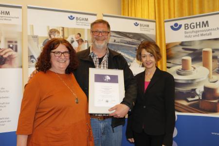 Frank Gaßmann (Gaßmann Gebäudetechnik GmbH) nimmt die Gütesiegel-Urkunde von Helene Weller (BGHM, links) und Silke Otto (BGHM, rechts) entgegen. (Quelle: BGHM)