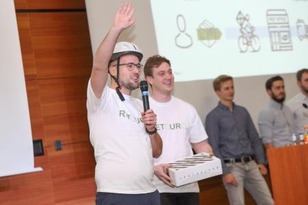 """Die Studierenden David Heid (links) und Robin Bässler (rechts) präsentieren ihre Idee """"Retouro – Wir erledigen Ihre Retoure: SMART und GRÜN!"""" beim Ideenwettbewerb """"stAArt-UP!de Challenge 2018"""", © Hochschule Aalen / Peter Schlipf"""