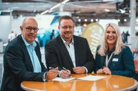 Ralf Kuhne, Vorstandsmitglied WM SE, Jochen Saße, easysub-Geschäftsführer, und Diana Rübsam, NFZ-Vertriebsleitung WM SE, strahlen bei der Vertragsunterzeichung um die Wette