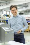 Sesotec Produktmanager Andreas Veicht freut sich, dass die neue Control Unit GENIUS ONE ab sofort für alle Freifall-Metalldetektoren der RAPID-Serie verfügbar ist und demonstriert die einfache Bedienbarkeit über das serienmäßige Touch Display.