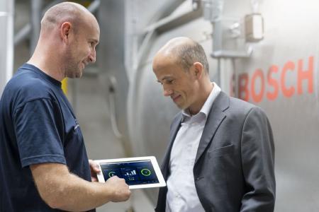 Bosch-Kundendiensttechniker Heiko Doppler zeigt Thomas Steffes von der ausführenden Firma Kramer & Best die verschiedenen Menüebenen von MEC Optimize. Der Effizienzassistent liefert künftig die Daten an die zentrale Leitwarte der Brauerei. (Bild: Bosch Industriekessel)
