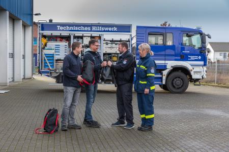 Die WEMAG-Mitarbeiter Remo Groß und Thoralf Taft überreichen dem THW-Zugführer Peter Burmeister-Schröder und Nicole Taft von der THW-Bergungsgruppe (v.l.) neun spezielle Schutzausrüstungen (Foto: WEMAG/Stephan Rudolph-Kramer)
