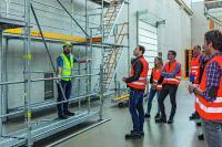 Brennpunkt aktuelle TRBS 2121-1. Hier wird die vorlaufende, zweiteilige Geländermontage in der Modulbauweise mit Vertikalstiel vorgeführt. (Foto: PERI GmbH)