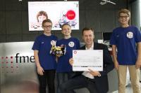 Dirk Bode, CEO der fme AG, überreicht Phil, Anton und Paul (v.l.n.r.) den Spendenscheck im Wert von 1.000 €