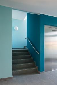 Das Treppenhaus des IT-Neubaus verbindet alle drei Stockwerke durch einen kräftigen hellen Blauton an den Wänden und einem Aufzugskern in dunklem Petrol (Foto: Caparol Farben Lacke Bautenschutz/Blitzwerk.de)