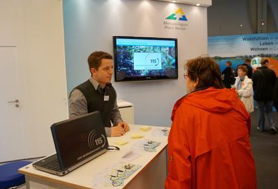 Mit verschiedenen Maßnahmen wird die einheitliche Behör-dennummer bekannt gemacht, hier mit einem Infostand beim Mannheimer Maimarkt 2013, Foto: Metropolregion Rhein-Neckar GmbH