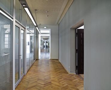 Die langen Flure wirken durch den neuen Parkettboden, die Beleuchtung und Glasfronten gemütlich, Foto: Caparol Farben Lacke Bautenschutz/Martin Duckek
