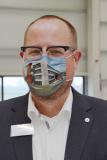 So sieht Vorfreude aus: AVENTUS-Geschäftsführer Kai Lammers trägt einen Mund-Nase-Schutz, bedruckt mit einer Visualisierung des AVENTUS-Neubaus.