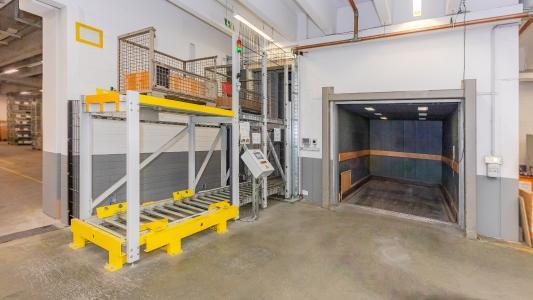 Der im bereits vorhandenen Schacht installierte Vertikalförderer dienst als Entlastung des bereits vorhandenen Lastenaufzugs.