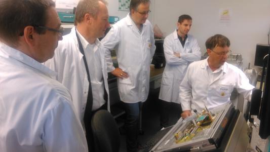 Produktionsleiter Albrecht Dietrich (rechts) erläutert den Teilnehmern am OPERTIS Partnertag den Incircuit-Tester