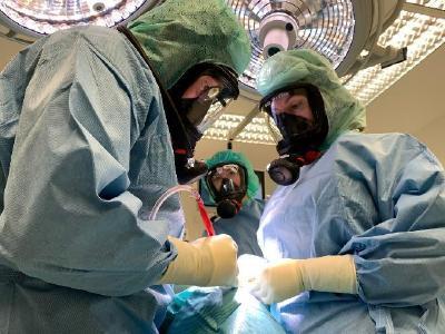 Ärzte operieren mit Vollschutzmasken der Feuerwehr während COVID-19-Pandemie wegen Engpässen bei der Beschaffung medizinischer Gesichtsmasken