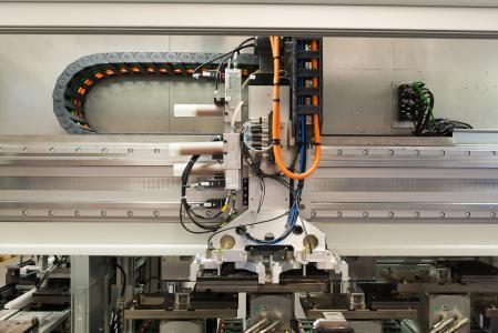 Kundenspezifische Linearmotorachse mit  2,8 Meter Länge: In einer Zykluszeit von 4,5 Sekunden  verteilt sie die Werkstückträger auf einen von acht Bestückungsplätzen