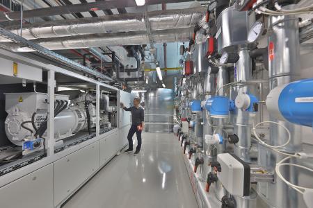 Blockheizkraftwerk und Warmwasserspeicher im Untergeschoss des Fraunhofer IISB: Die Kraftwärme-Kopplungsanlage wurde im Rahmen des Erweiterungsbaus B in die Infrastruktur des Instituts integriert. Dort wird sie sowohl zur Wärme- und Stromversorgung als auch als Forschungsanlage genutzt. Bild: Kurt Fuchs / Fraunhofer IISB