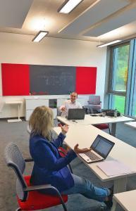 Marion Wagner, Strategy & Coordinaton Manager Group Technology Partnerships eMotorsports, und Andreas Nadler, Field Application Engineer (beide Würth Elektronik eiSos), sitzen virtuell mit den Entwicklern des Sonnenwagen Aachen e. V. im Seminarraum zusammen / Bildquelle: Würth Elektronik