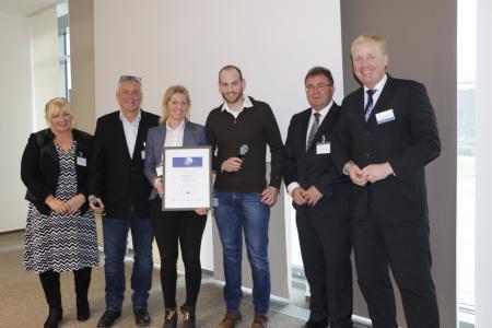 Familie Schütz vom Unternehmen Dimos Maschinenbau GmbH erhält die Gütesiegel-Urkunde von Detlef Guyot, BGHM (links). (Quelle: BGHM)
