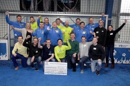 Jens Teichler von ITK Engineering (1. Reihe, 3. v. l.) übergibt den Spendenscheck an Tina Klose (1. Reihe, Mitte) und das Team von Sportfreunde Braunschweig e.V. beim 7. Sportfreunde Cup in Braunschweig / Foto: ITK Engineering