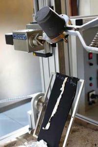 Das verflüssigte Metall wird in einer Vorrichtung maschinell nach festgelegten Standards auf das Prüfmaterial aufgebracht. Damit werden der Auftreffwinkel und die Fließgeschwindigkeit des flüssigen Metalls bei allen Prüfdurchläufen reproduzierbar.