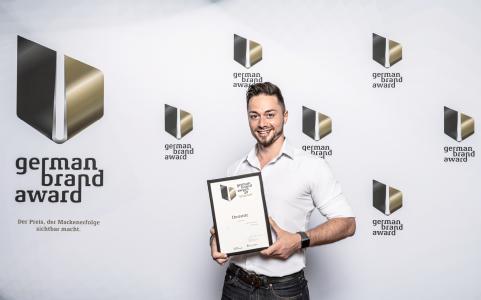 Dominic Fischer, Eventmarketing Manager bei Dematic, nahm gestern in Berlin den German Brand Award für Dematic entgegen. (Foto: German Brand Award)