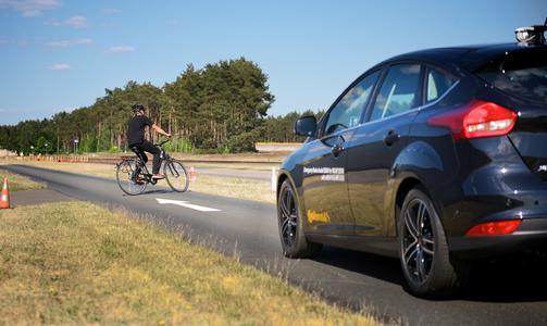 Ein Demofahrzeug mit Radarsensor und Kamera ausgestattet erfasst mit den Sensoren einen Radfahrer und warnt sobald sich dieser im Fahrschlauch des Fahrzeugs befindet
