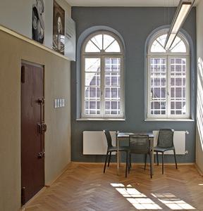 Die vergitterten Fenster, hier die Rundbogenfenster an der Stirnseite der Flure, erinnern an die frühere Nutzung als Gefängnis. Die Stirnseiten wurden in der Kennfarbe des jeweiligen Stockwerks gestaltet, Foto: Caparol Farben Lacke Bautenschutz/Martin Duckek