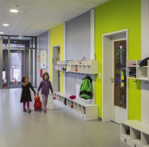 Gelb, Grün oder Blau? Die markanten Einfassungsflächen um die Türen helfen den Kindern, ihren Gruppenraum schnell zu erkennen. Die jeweilige Kennfarbe wiederholt sich auf einer der verputzten Wände im Raum (Foto: Caparol Farben Lacke Bautenschutz/Martin Duckek)